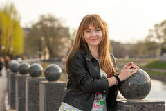 Beautiful young city woman. Portrait of a beautiful young girl near the ball stone in the city park Royalty Free Stock Photography