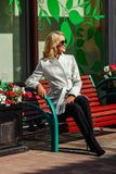 The beautiful young city woman in a beige coat sits on a bench stock photo