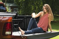 Beautiful country girl on back of pick-up truck. Beautiful young country girl poses with jar of lemonade in back of pickup truck on farm wearing blue jeans Royalty Free Stock Photo