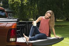 Beautiful country girl on back of pick-up truck. Beautiful young country girl poses with jar of lemonade in back of pickup truck on farm wearing blue jeans Stock Images