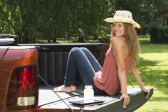 Beautiful country girl on back of pick-up truck. Beautiful young country girl poses with jar of lemonade in back of pickup truck on farm wearing blue jeans and Royalty Free Stock Images