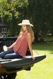 Beautiful country girl on back of pick-up truck. Beautiful young country girl poses with jar of lemonade in back of pickup truck on farm wearing blue jeans and Stock Photos