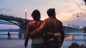 Beautiful young couple against the backdrop of a colorful sunset and city lights. Romantic atmosphere. Two lovers