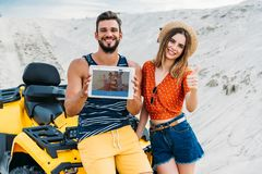 beautiful young couple with atv showing digital tablet with couchsurfing website on screen and thumb up royalty free stock images