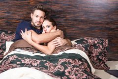 Beautiful young couple being scared in bed Stock Image