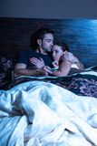 Beautiful young couple being scared in bed Royalty Free Stock Photography