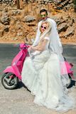 Beautiful young couple, blonde female model with her husband in amazing wedding clothes sitting on scooter Stock Image