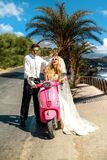 Beautiful young couple, blonde female model with her husband in amazing wedding clothes sitting on scooter Stock Photos