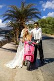 Beautiful young couple, blonde female model with her husband in amazing wedding clothes sitting on scooter Stock Photo