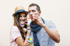 Beautiful young couple blowing soap bubbles. Stock Photography