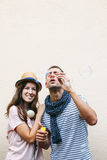 Beautiful young couple blowing soap bubbles. Stock Photos