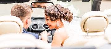 Beautiful young couple bride and groom posing in cabriolet Stock Photography