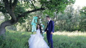 Beautiful young couple bride and groom in a. Wedding dress on a swing in the  park stock video