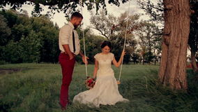 Beautiful young couple bride and groom in a. Wedding dress on a swing in the park at dusk,  European wedding stock video