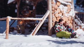 Beautiful young couple in bright colorful ski-costumes. Lovely couple sitting by the wooden storage and passionately stock video