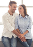 Beautiful young couple. Beautiful young business couple in classic shirts is holding hands, looking at each other and smiling while sitting on the window-sill Stock Photos