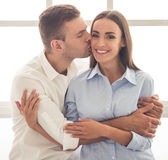 Beautiful young couple. Beautiful young business couple in classic shirts is sitting near the window. Man is hugging and kissing his girl in cheek while she is Stock Photos
