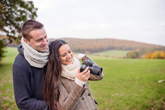 Beautiful young couple with camera taking pictures. Autumn natur. Beautiful young couple with camera taking pictures of sunny autumn nature Stock Image