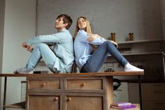 Beautiful young couple in casual cloth sitting on the table royalty free stock images