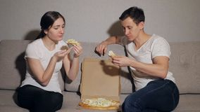 Beautiful young couple in casual clothes are eating pizza. Drinking, talking and smiling stock video footage