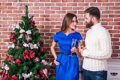 Beautiful young couple is celebrating christmas at home. Look at each other eyes and smiling. Stock Images