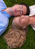Beautiful young couple cheek to cheek in grass Royalty Free Stock Photos