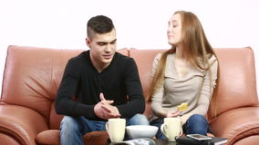 Beautiful young couple conflict sitting on a couch argue unhappy. Portrait young man and woman stock video