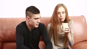 Beautiful young couple conflict sitting on a couch argue unhappy. young man and woman. Beautiful young couple conflict sitting on a couch argue unhappy, portrait stock video
