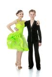 Beautiful young couple dancing. In bright clothes for competitions hugging and posing for the camera-Isolated on white Royalty Free Stock Image