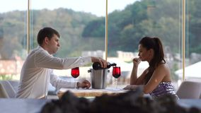 Beautiful young couple at date in luxury restaurant. The elegant man is pouring red wine in glasses. stock video footage