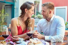 Young couple on a date looking at each other. Beautiful young couple on a date in restaurant looking at each other royalty free stock photography