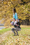 Beautiful young couple doing squats together in the park. Autumn environment Royalty Free Stock Photography