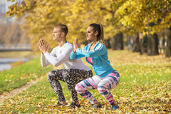 Beautiful young couple doing squats together in the park. Autumn environment Stock Image