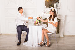 Beautiful young couple drink coffee hold cup, happy smile looking each other. Royalty Free Stock Photography
