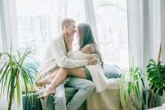 Beautiful young couple is drinking coffee, talking and smiling while sitting near the window. At home Stock Photos