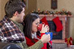 Beautiful young couple drinking tea in Christmas night. Young romantic couple in Christmas night royalty free stock images