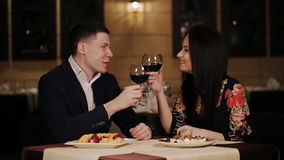 Beautiful young couple is drinking wine, talking and smiling at the restaurant. Love, dating, people and holidays concept - smiling couple clinking glasses of stock footage