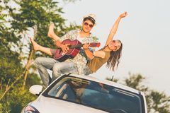 Beautiful young couple enjoying on car roof against and singing their favorite song royalty free stock image