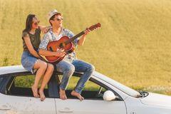Beautiful young couple enjoying on car roof against yellow field background. royalty free stock photos