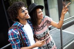Beautiful young couple enjoying in good mood in city. Lifestyle, love, dating, vacation concept. Summer time. Beautiful young african couple dating and smiling royalty free stock photos