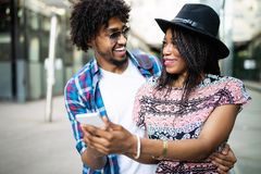 Beautiful young couple enjoying in good mood in city. Lifestyle, love, dating, vacation concept. Summer time. Beautiful young african couple dating and smiling stock image