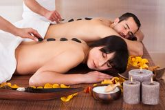 Beautiful young couple enjoying hot stone therapy Royalty Free Stock Photos