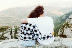 Beautiful young couple enjoying nature at mountain peak. Portrait of beautiful young couple enjoying nature at mountain peak Stock Photo