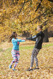 Beautiful young couple enjoying and rotating together in the park. Autumn environment Royalty Free Stock Image