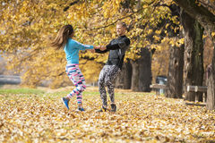 Beautiful young couple enjoying and rotating together in the park. Autumn environment Stock Photo