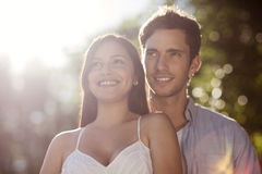 Beautiful young couple enjoying the sun. Beautiful young couple standing together outdoors in the sun Royalty Free Stock Photography