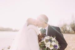 Beautiful young couple enjoying sunset, kissing on river coast Stock Images