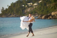 Beautiful young couple enjoying sunset, walking barefoot on beach and playing with each other. Lifestyle wedding on tropical island in caribbean or Hawaii stock photos