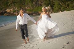 Beautiful young couple enjoying sunset, walking barefoot on beach and playing with each other. Lifestyle wedding on tropical island in caribbean or Hawaii stock images