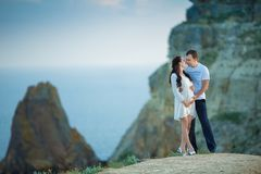 Beautiful young couple expecting baby posing on mountain view with blue sea as background royalty free stock photo